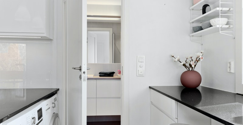 Plass til vaskemaskin i kjøkkenøya. Inngang til bad.