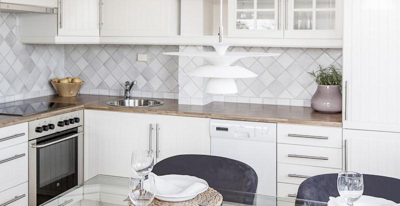 Kjøkkenet har rikelig med skap- og benkeplass, samt plass til spisebord og utgang til balkong på 3 kvm.