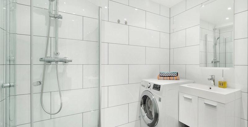 Stort og moderne flislagt bad med varmekabler i gulv.