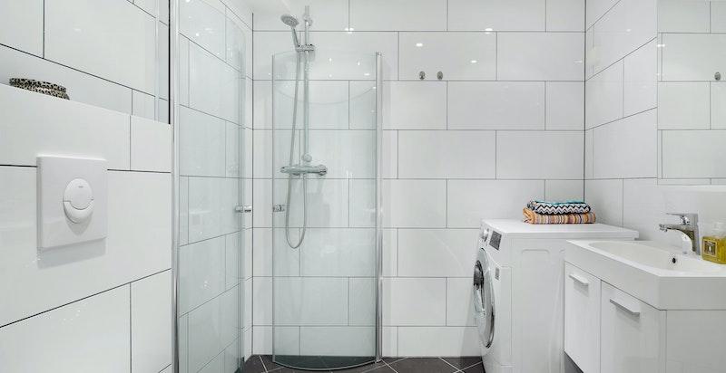 Badet inneholder vegghengt wc, dushjørne, servant og opplegg til vaskemaskin/tøretrommel.