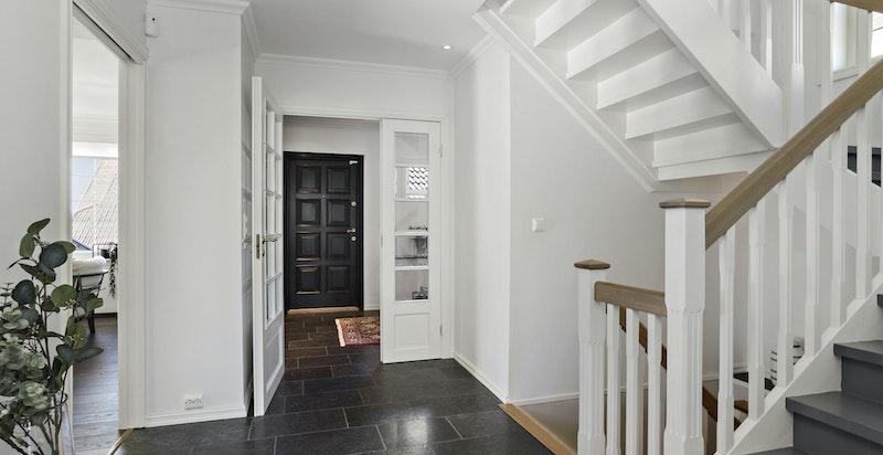 Hall med trapp til kjelleretasjen og opp til soveromsetasjen