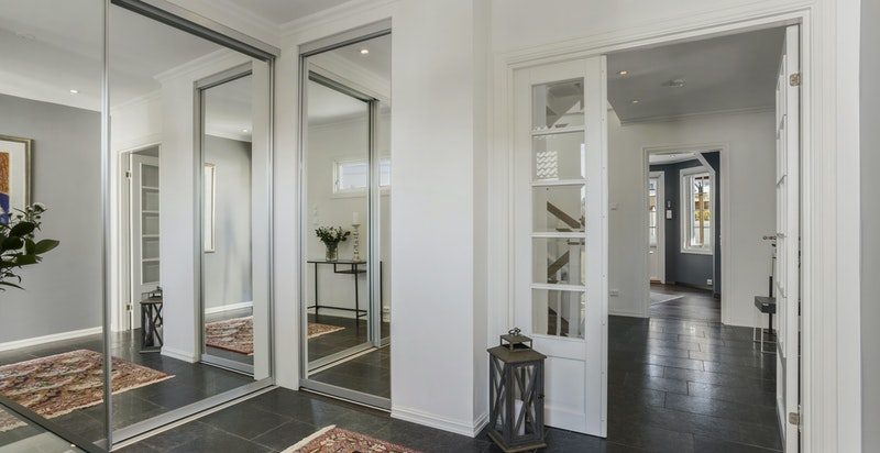 Romslig hall med dype garderober - flislagt gulv