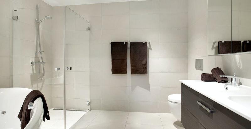Sort baderom med dushjørne og badekar