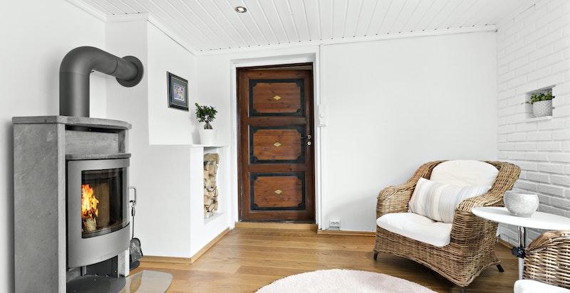 Den første stuen har peisovn og adkomst til bod og egen utgang til gårdsplassen. Legg merke til den vakre, originale døren som er beholdt
