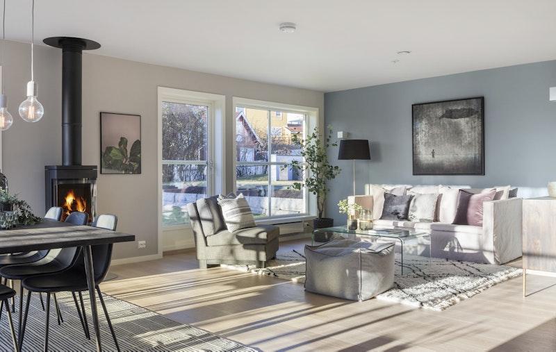 Lys og åpen stue med peis og utgang til hage