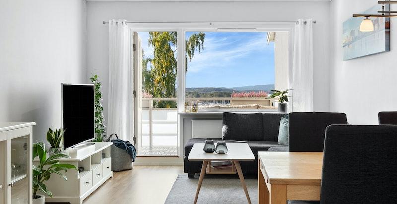 Stue med utgang til solrik balkong og flott fjordutsikt