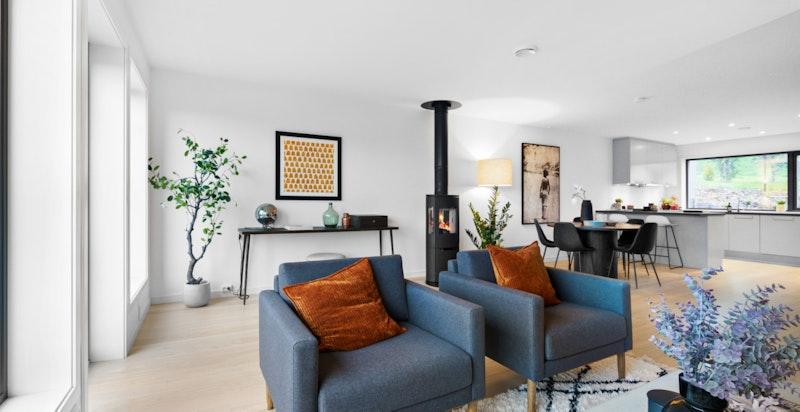 Meget lys stue. Peisovn står sentral og godt synlig fra både stue, spisestue og kjøkken.