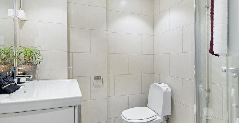 Pent flislagt bad antatt fra 2001/02 med dusjhørne, servant på skapinnredning og toalett - Varmekabler - Ny termostat til varmekablene fra 2017