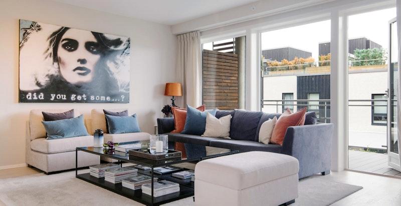 Romslig lys stue med store vindusflater