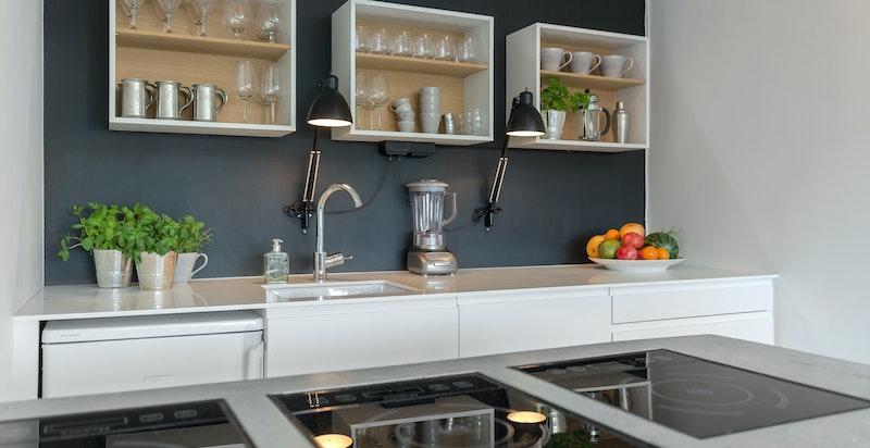 Kjøkkenøy av støpt betong. Kjøkkenet har integrerte hvitevarer.