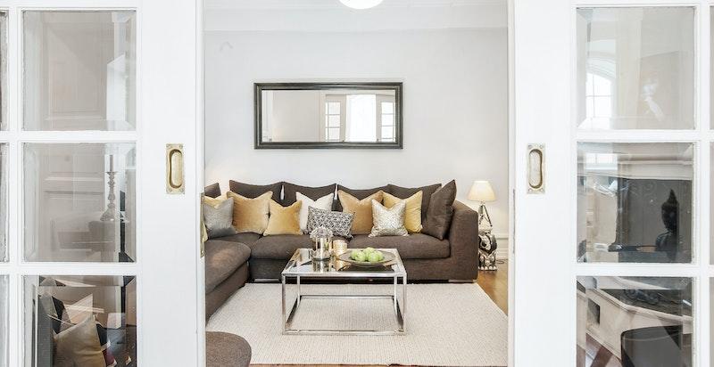 Koselig tv-stue II med peis der late kvelder kan nytes, adskilt med klassiske skyvedører til spisestuen.