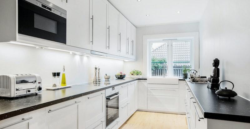Kjøkkenet har rikelig med skuffer, skap og benkeplass. Et stort vindu gjør rommet til en lys og trivelig arbeidsplass.