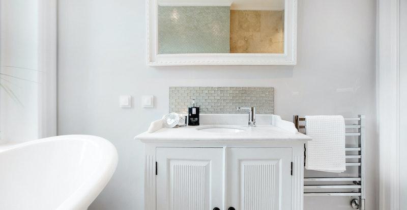 Flott, frittstående servantskap med benkeplate i marmor og underlimt vask i engelsk stil.