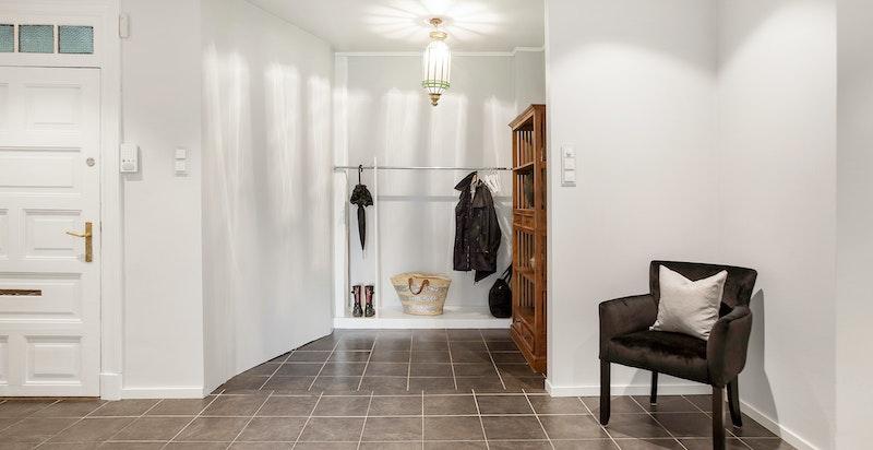 Entreen har god takhøyde, flislagt gulv med v. kabler og nymalte vegger. Åpen garderobeløsning.