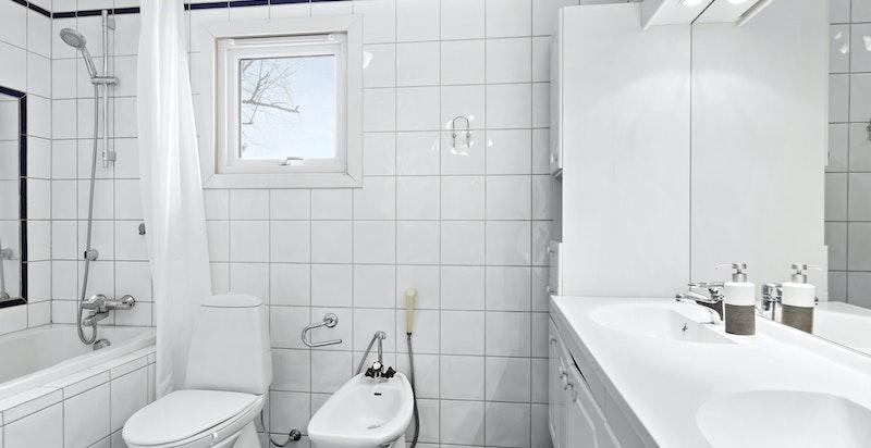 Baderom i tilknytning til hovedsoverommet. Innfliset badekar med speil langs veggen, bidét, wc og dobbelservant i innredningen.