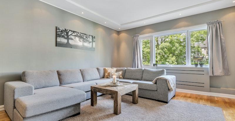 Stor og lys stue med utsyn mot stille bakgård