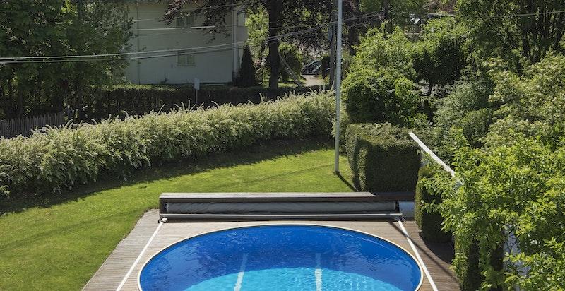 Utsikt mot svømmebassenget (6,4 x 8,5 m) og hagen fra 2. etasje.