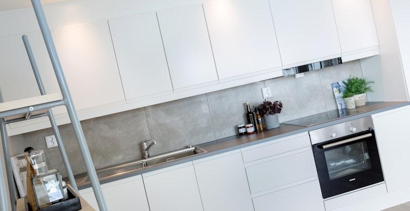 Detalj kjøkken. Tidsriktige fliser over kjøkkenbenk og downlights over kjøkkenskap.