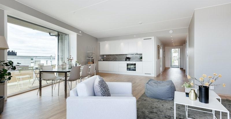 Lys og romslig oppholdssone med kjøkken åpent mot stue. Naturlige soner for møblering.