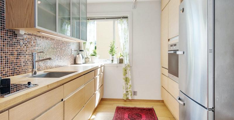 Kjøkken med morgenlys og utsyn mot felles grønn hage.
