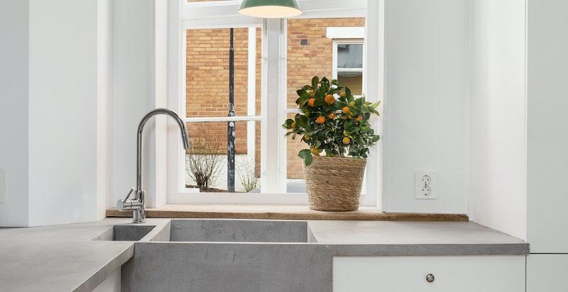 Kjøkken med støpt benkeplate og vask i betong