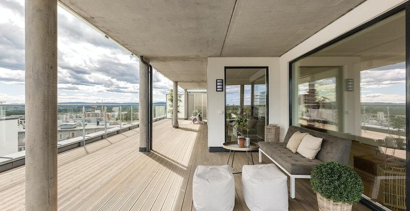 Den store terrassen har plass til flere salonger og har naturlige soner for møblering.