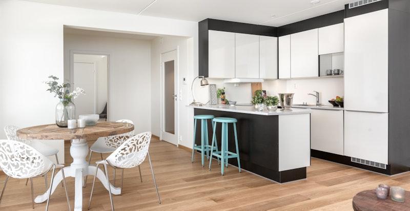 Åpen løsning med påkostet kjøkken fra HTH med sitteøy som tilrettelegger for en sosial arena.
