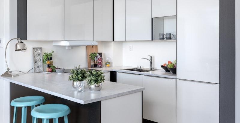 Påkostet og tiltalende kjøkken fra HTH med hvite høyglans fronter og sorte elementer i stilig kombinasjon.