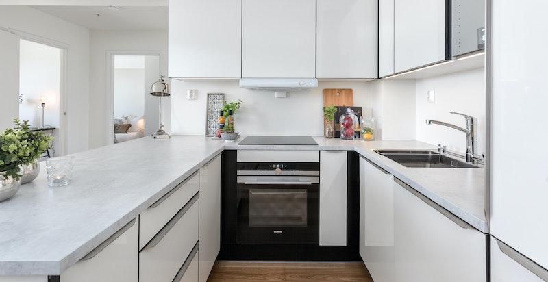 Kjøkkenet er utstyrt med laminatbenkeplate i modellen Hvit Betong, underlimt stålvask, ettgrepsarmatur, stikkontakt og slimline ventilator.