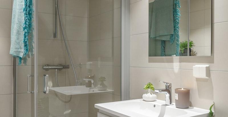 Badet er utstyrt med hvit baderomsinnredning med heldekkede servantplate og to skuffer, speil over servant, ettgrepsarmatur og stikkontakt. Videre har badet vegghengt toalett, dusjhjørne med innfellbare dusjvegger i glass og opplegg for vaskemaskin/tørk.