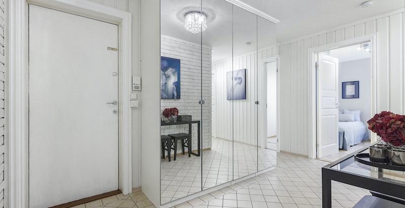Romslig entrè/ gang med stor garderobeskap med speildør fra gulv til tak
