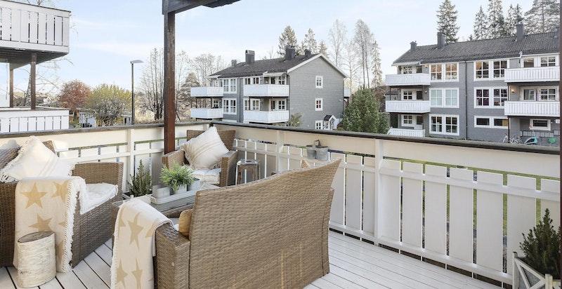 Romslig, overbygget veranda med utsyn mot fellesarealer
