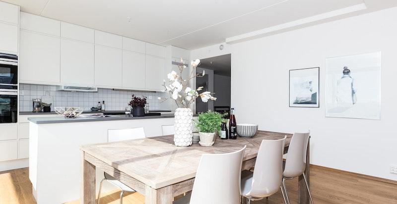 Kjøkkenet er stilrent og er praktisk designet med gode arbeidsflater og en praktisk kjøkkenøy som også fungerer som en naturlig romdeler mellom kjøkken og stue/spisestue.
