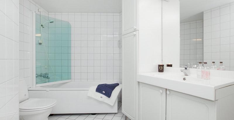 -Flislagt bad med badekar og rikelig med baderomsinnredning