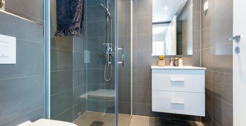 Delikat dusjbad med italienske fliser, varmekabler og downlightsbelysning.