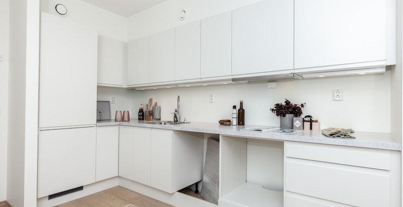 Kjøkkenet er utstyrt med 40mm laminatbenkeplate i modellen Hvit Betong fra Sigdal, underlimt stålvask, ettgreps uttrekksarmatur og slimline ventilator.