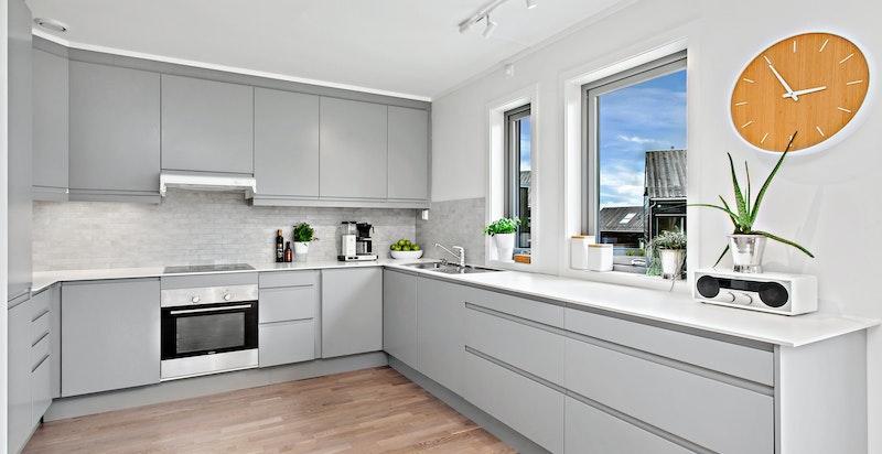 Pent kjøkken med store vinduer ut mot hage