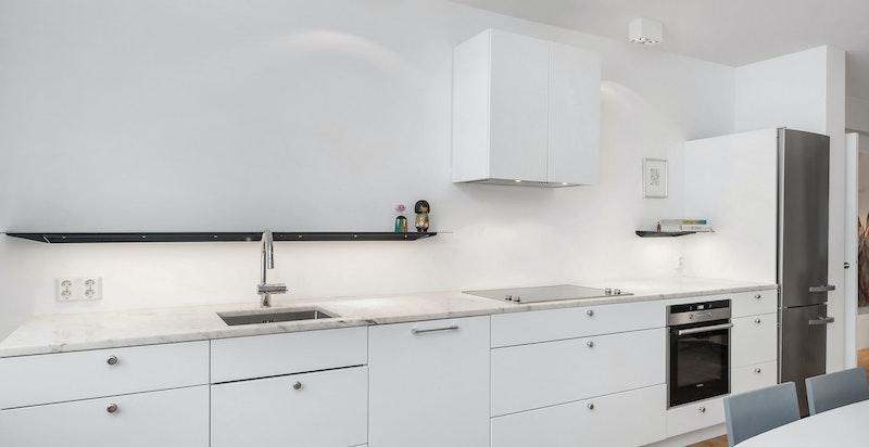 Kjøkken - integrerte hvitevarer fra Miele og Siemens. Spesialdesignede stålhyller m/ ledbelysning.