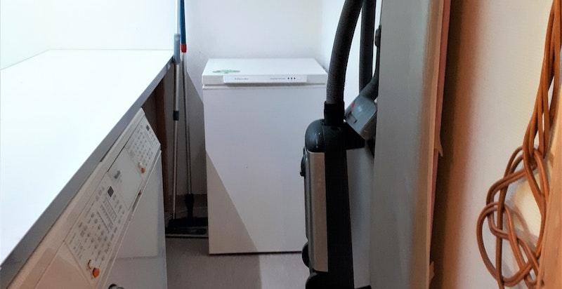 Praktisk vaskerom innenfor kjøkkenet med benk og hyller.