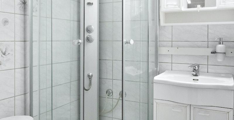 Flislagt bad med dusjkabinett, servant med skap og speilskap.