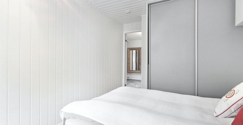 Hvitmalte panelplater på vegg og laminat på gulv.