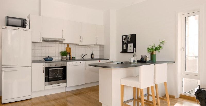 Kjøkken med praktisk øy for mer oppbevaring og spiseplass.