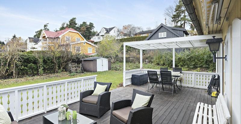 Terrasse og hage mot sydvest - skjermet med hekk og beplantning. Uthus/redskapsbod.