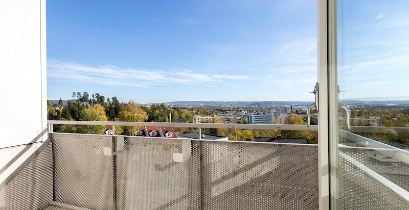 Flott solrik balkong med utsikt mot fjorden og byen.