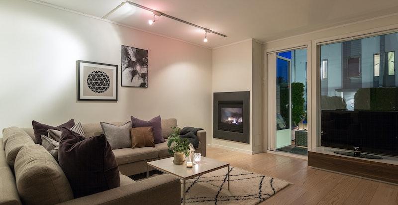 Stue med gasspeis og utgang til terrasse og hage.