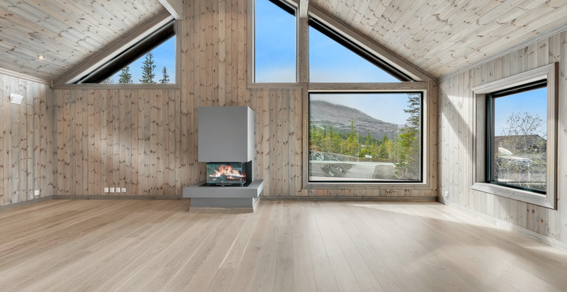Stor stue og kjøkkendel med herlig takhøyde og lekre vindusløsninger