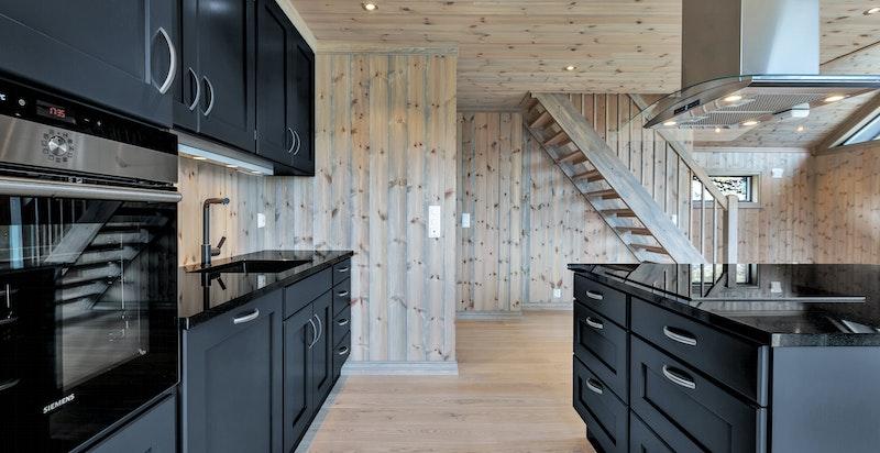 Moderne kjøkkeninnredning og store vindusflater mot utsikten