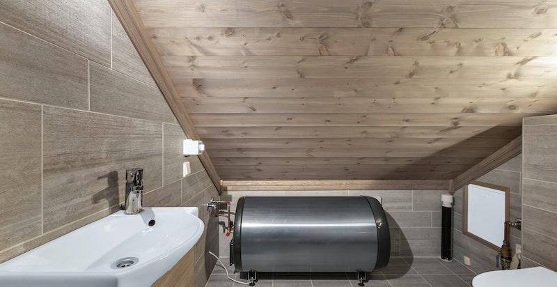 Gråspettede fliser på gulv og vegg - lagt i omvekslende mønster på vegg.
