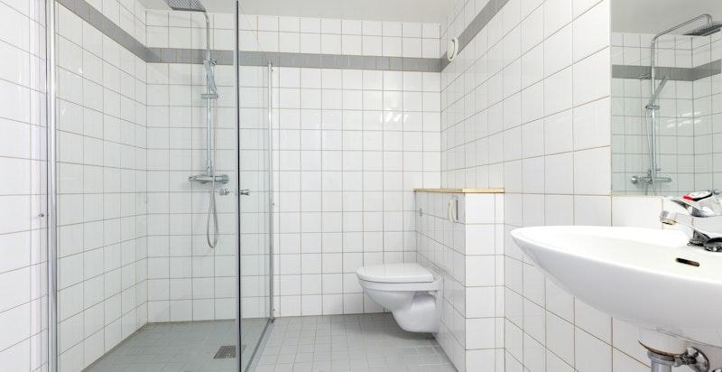 Pent flislagt bad med gulvvarme, dusjhjørne og opplegg for vaskemaskin/tørketrommel.