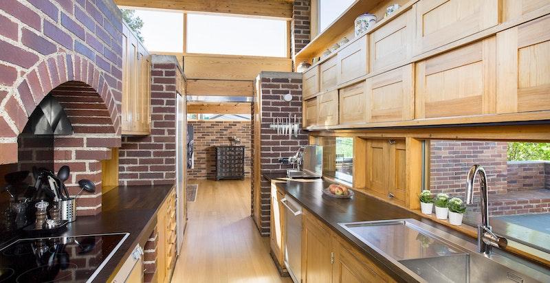 Kjøkkenet ligger midt i boligen med direkte adkomst til stuen på den ene siden og spisestuen på den andre siden